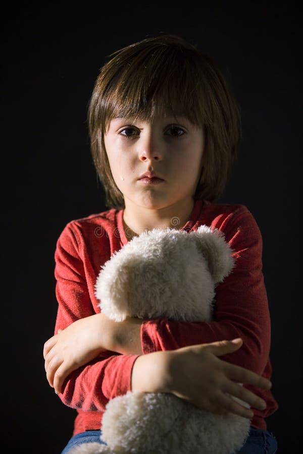 Ledset litet barn, gråt som kramar den välfyllda leksaken arkivfoto