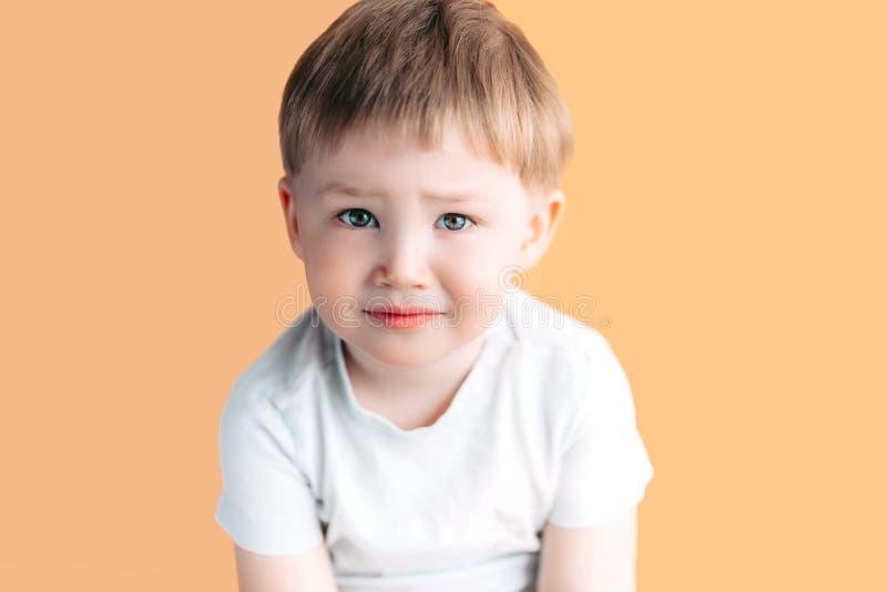 Ledset och att tänka Deprimerad Closeupståendeheadshot, bara, trött barn på orange bakgrund Negativ mänsklig sinnesrörelseframsid arkivbilder