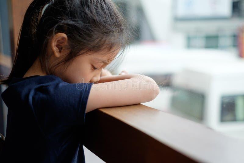 Ledset och ensamt asiatiskt barn bredvid fönster royaltyfria bilder
