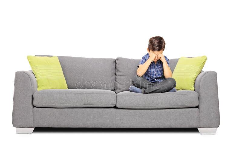 Ledset pojkesammanträde på en soffa och en gråt fotografering för bildbyråer