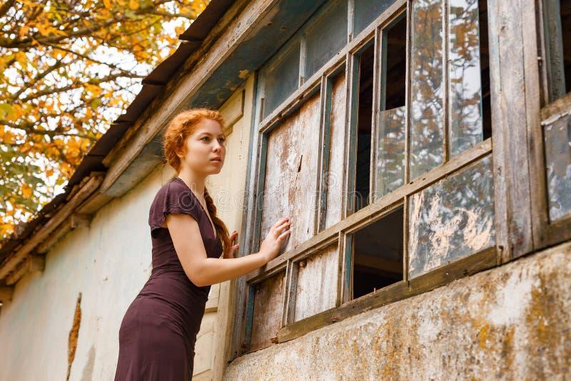 Ledset rödhårigt flickaanseende nära ett brutet fönster, begreppet av armod och misär fotografering för bildbyråer