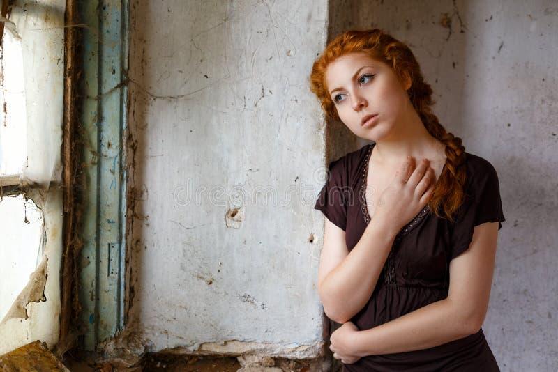 Ledset rödhårigt flickaanseende nära ett brutet fönster, begreppet av armod och misär royaltyfria bilder