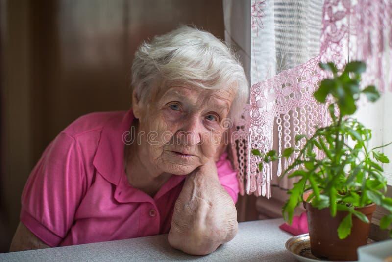 Ledset sammanträde för äldre kvinna på tabellen royaltyfria foton
