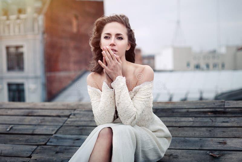 Ledset sammanträde för härlig flicka på taket Ensam kvinna i deprimerande lynne på taket royaltyfri fotografi