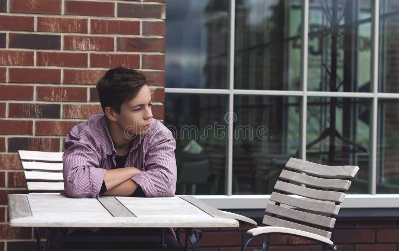 Ledset sammanträde för ung man på en tabell nära en vägg royaltyfri foto