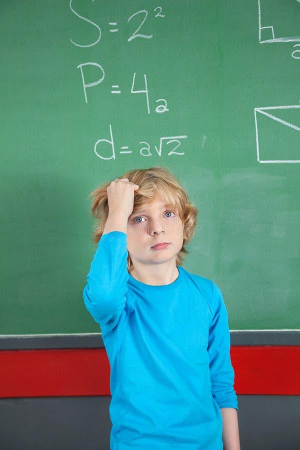 Ledset skolpojkeanseende mot bräde i klassrum royaltyfria bilder