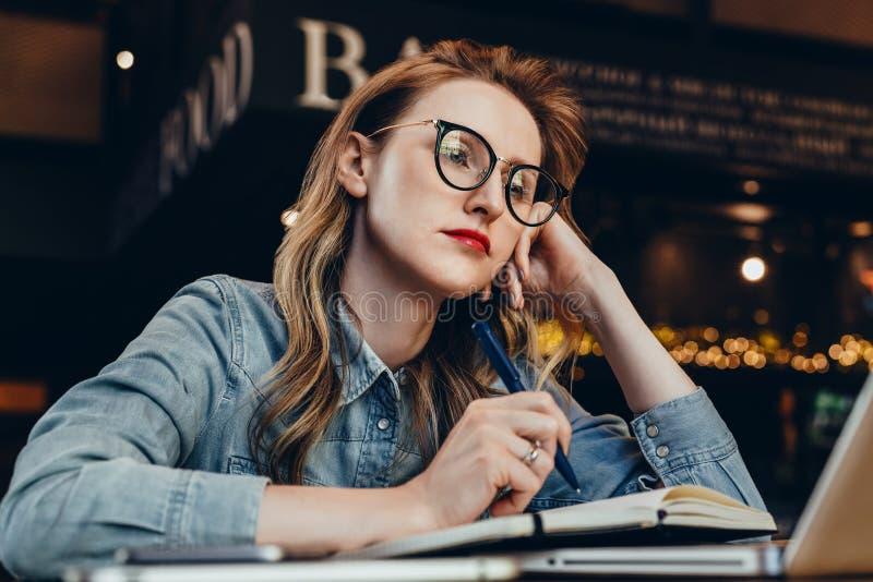 Ledset studentflickasammanträde i kafé framme av bärbara datorn som förbereder sig för examina Kvinnan tar tråkig online-utbildni fotografering för bildbyråer