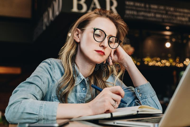Ledset studentflickasammanträde i kafé framme av bärbara datorn som förbereder sig för examina Kvinnan tar tråkig online-utbildni arkivbild