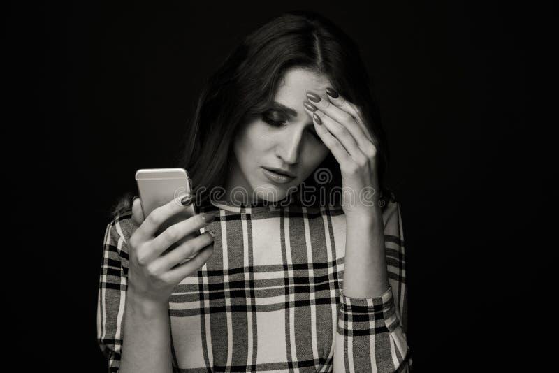 Ledset ton?rigt vara offer av cyberen som trakasserar online-sammantr?de p? en soffa i vardagsrummet p? royaltyfri foto