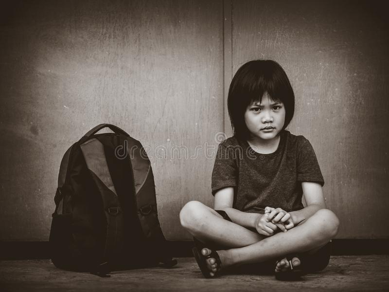Ledset ungesammanträde på golvet med den väntande på föräldern för skolapåse royaltyfri foto