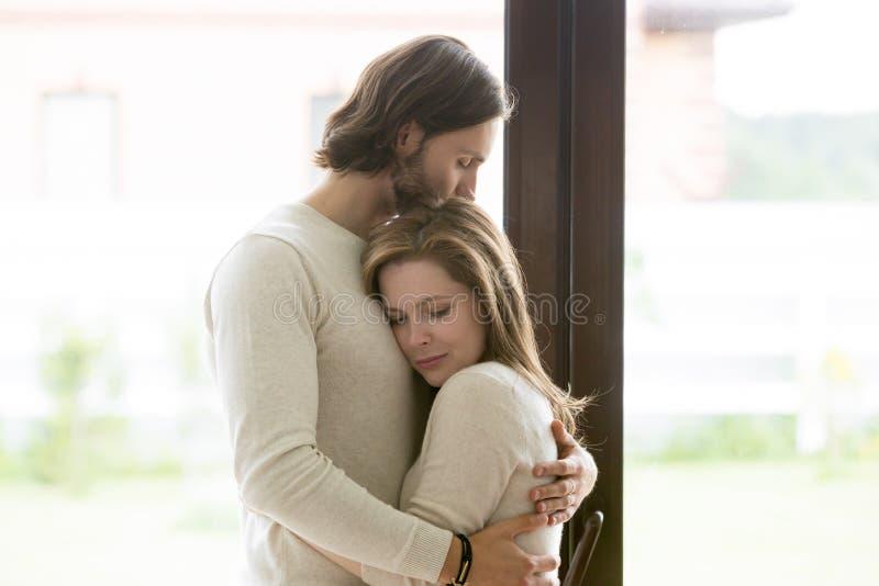 Ledset ungt gift par som omfamnar anseende i vardagsrum arkivbild