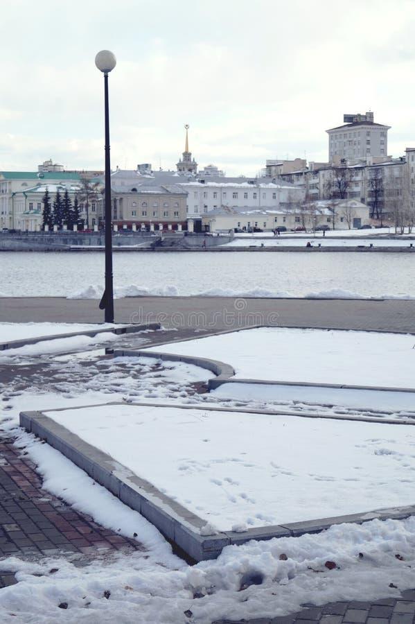 Ledset vinterlandskap Lykta koncentrisk blomsterrabatt, flod, drivor, stadsbyggnader i avståndet royaltyfria foton