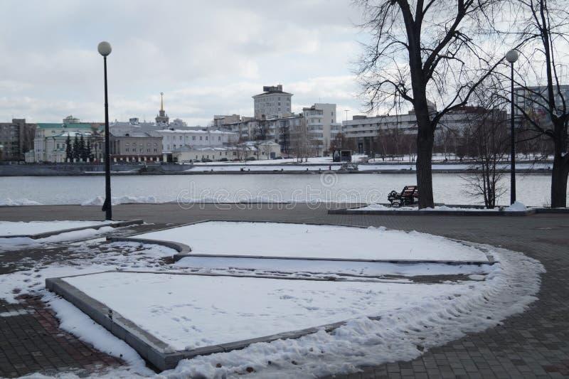 Ledset vinterlandskap Lykta koncentrisk blomsterrabatt, flod, drivor, stadsbyggnader i avståndet arkivfoto