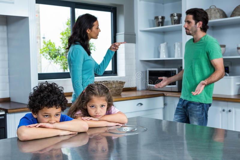 Ledsna barn som lyssnar till förälderargumentet royaltyfria bilder