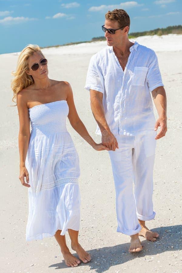 Ledsna kvinnapar för ung man som går på en strand royaltyfria foton