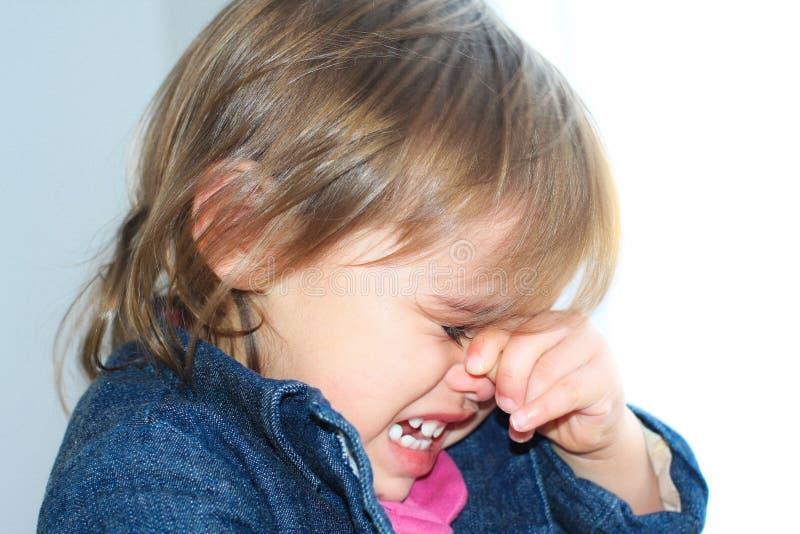 Ledsna litet barnflickarubs synar och gråter royaltyfri foto
