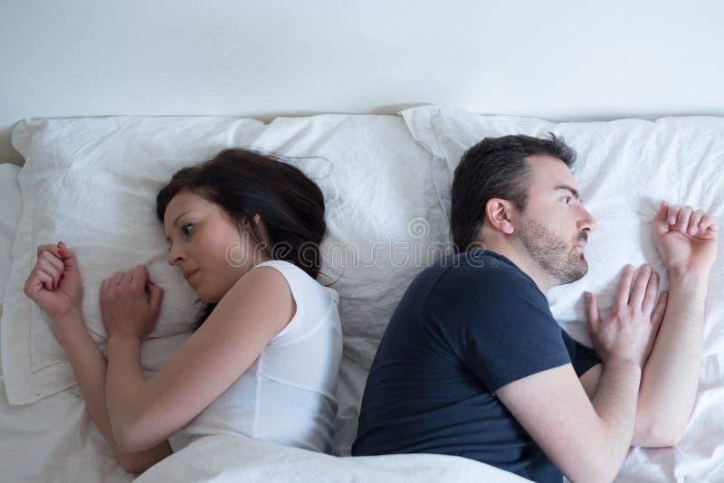 Ledsna och fundersamma par, når att ha argumenterat att ligga i säng arkivbilder