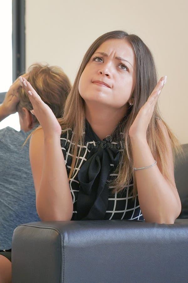 Ledsna par efter argument eller upplösning som inomhus sitter på en soffa i vardagsrummet i ett hus arkivbilder