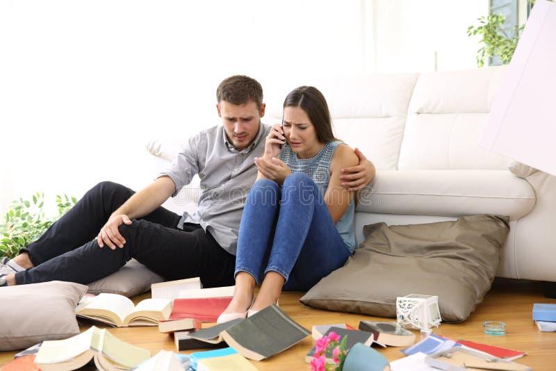 Ledsna par som kallar för att övervaka efter hem- röveri royaltyfri bild