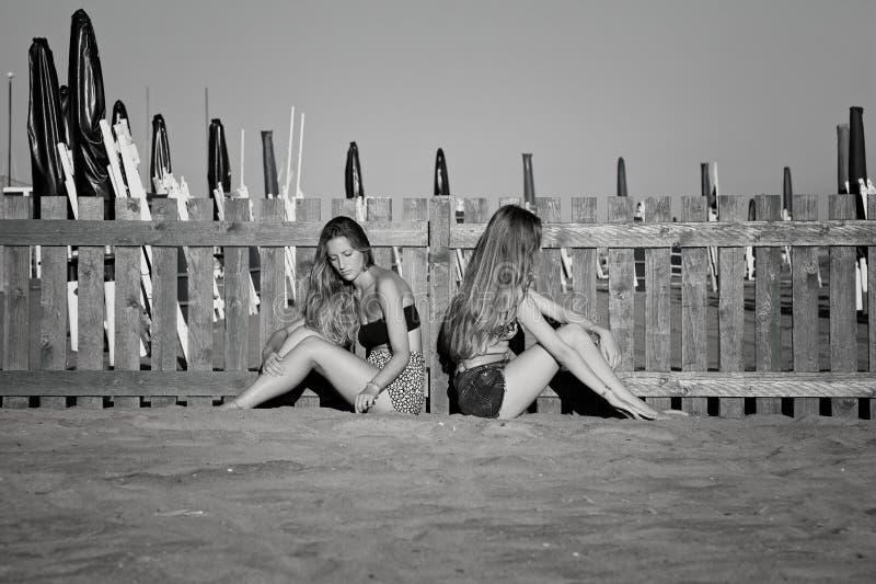 Ledsna tonåringar i tystnad på stranden som inte talar efter den svartvita kampen arkivbilder
