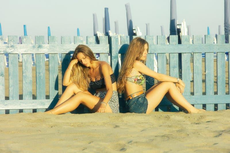 Ledsna tonåringar i tystnad på stranden som inte talar efter kamp royaltyfri fotografi