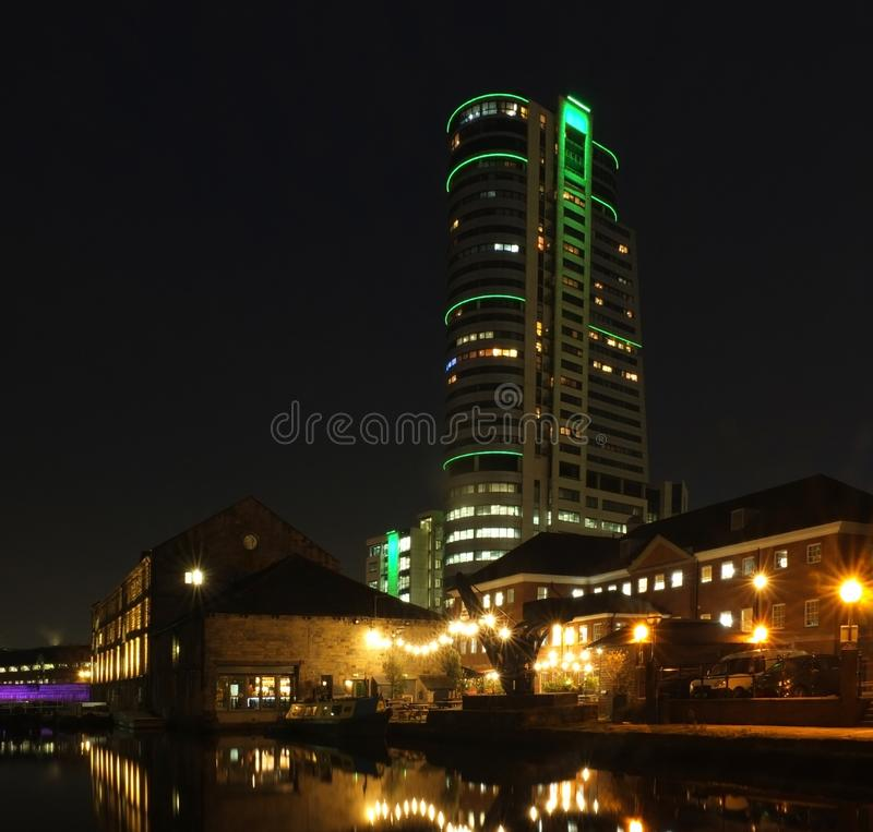 Leeds canal wharf at night with brightly illuminated buildings and lock reflected in the water and glowing against a dark sky stock images