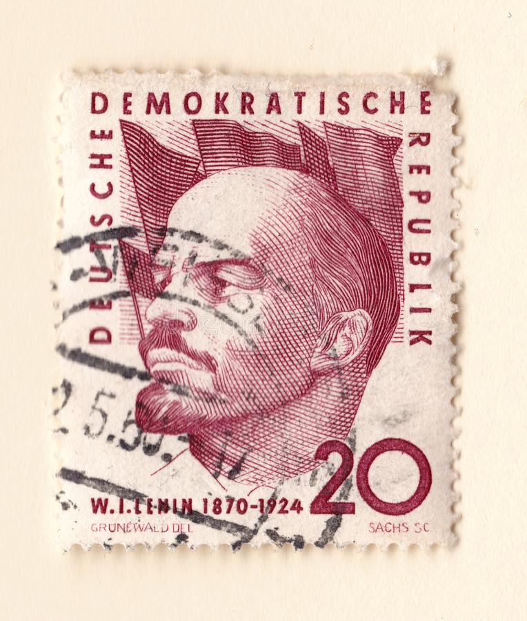 An old red east german stamp with n image of lenin with a background of flags stock photography