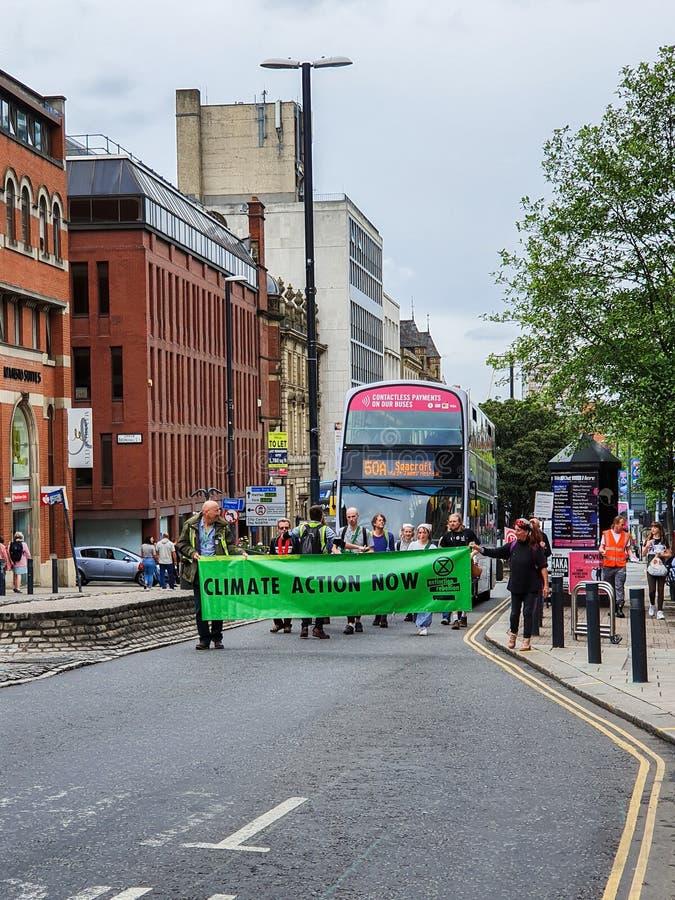 LEEDS, REINO UNIDO - 1 DE JUNIO DE 2019: Un grupo de manifestantes soporta tr?fico que protestan sobre cambio de clima en centro  imagen de archivo libre de regalías