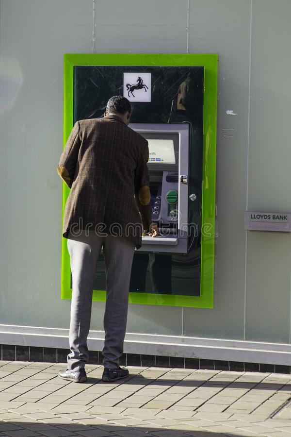 Lloyds Bank Cash Machine being used by asian man stock photo