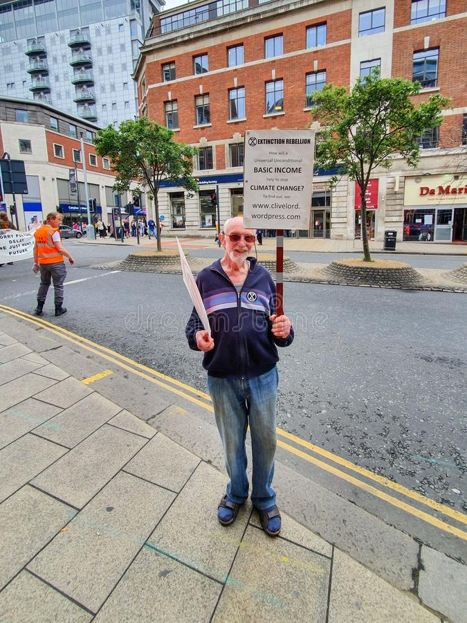 LEEDS, UK - 1ST JUNE 2019: An elderly gentleman protests about climate change in Leeds city centre holding signs up stock photography