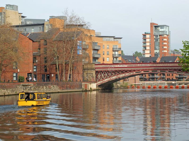 a yellow water taxi boat passing under crown point bridge over the river aire in leeds stock photos