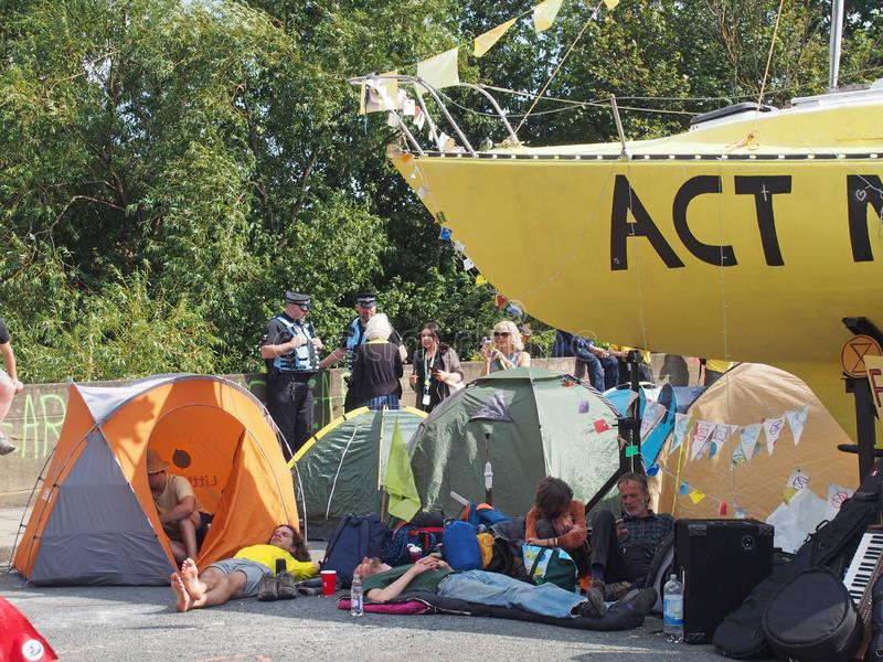 People around tents and the boat at the extinction rebellion protest blocking the road at victoria bridge in leeds royalty free stock photography