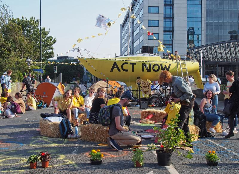People sitting around the boat and tents blocking the road bridgewater place in leeds during an extinction rebellion protest stock photos