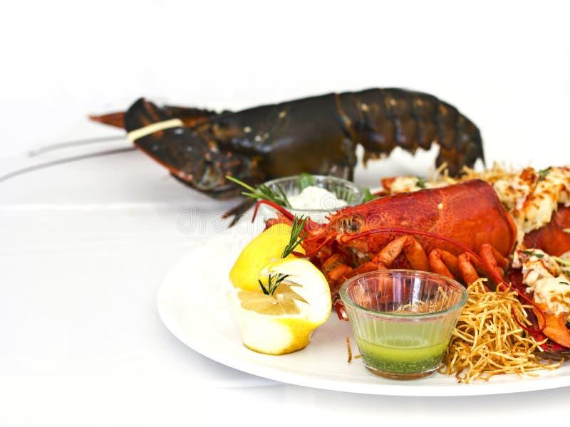 Leef en kookte zeekreeft met groenten op een witte plaat Isolat royalty-vrije stock foto