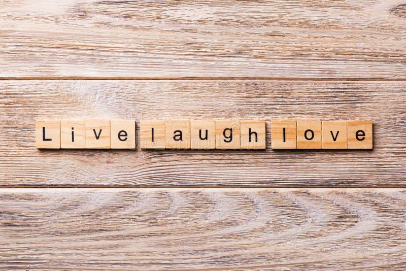 Leef het woord van de lachliefde op houtsnede wordt geschreven die Leef de tekst van de lachliefde op houten lijst voor uw het de stock foto