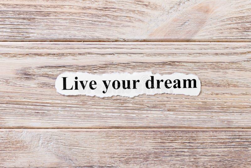 Leef uw droom van het woord op papier Concept Woorden van levend uw droom op een houten achtergrond stock foto's