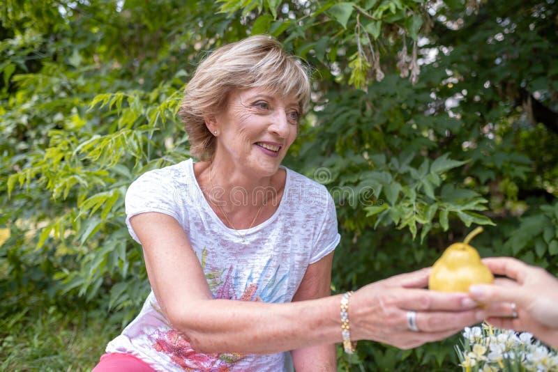 Leeftijd, het gezonde eten, voedsel, dieet en mensenconcept - sluit omhoog van gelukkige glimlachende hogere vrouw met peer stock foto