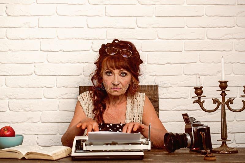 Leeftijdsbarrière Het journalistwerk in uitstekend bureau Het oude vrouwenwerk in schrijversbureau Hoger vrouwentype op retro sch stock foto