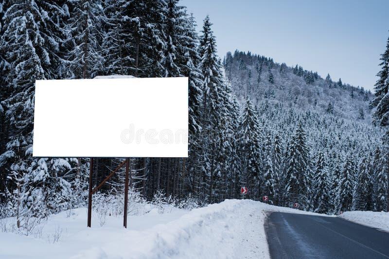 Leeg aanplakbord voor de reclame van affiche op de achtergrond van sneeuwbomen Wintertijd op een bergachtig gebied stock foto's