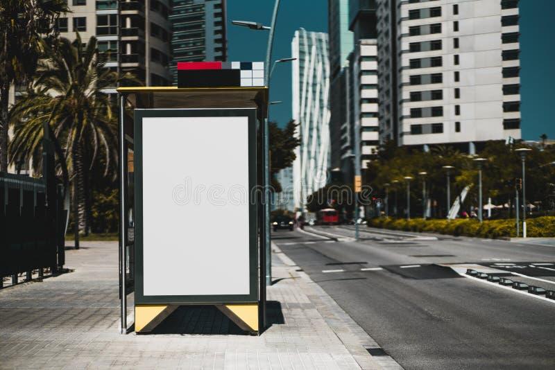 Leeg aanplakbordplaceholder malplaatje op de bushalte met de weg op het recht; het lege prototype van de reclamebanner in stedeli stock foto's