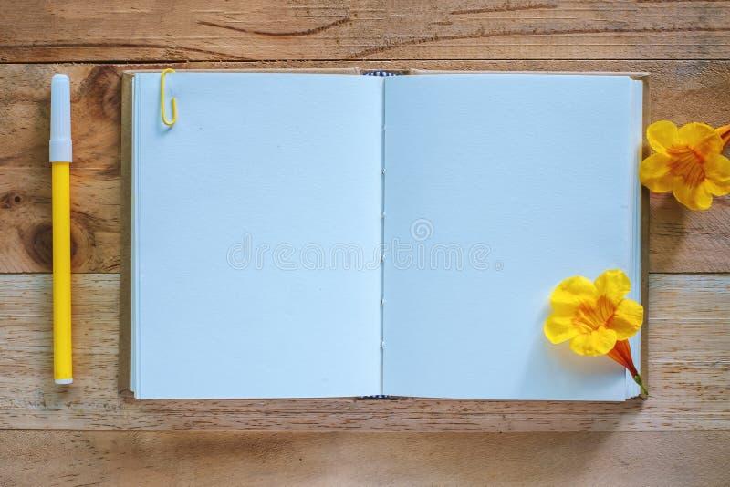 Leeg agendanotitieboekje, gele bloem en pen op houten lijst stock afbeeldingen