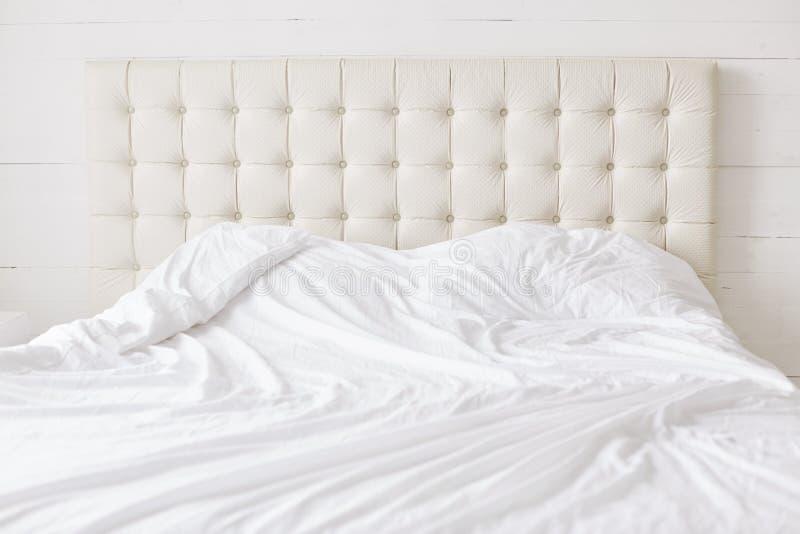 Leeg bed met wit zacht dekbed met niemand Ruime slaapkamer en comfortabel bed voor uw ontspanning en rust concept van de Bedtijd royalty-vrije stock afbeeldingen