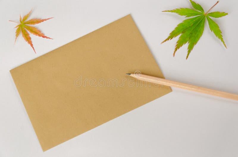 Leeg blad bruin bewerkt document voor groettekst, een potlood en twee de herfstbladeren op witte achtergrond De ruimte van het ex royalty-vrije stock foto's