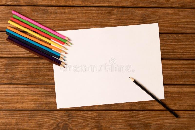 Leeg blad van document met een reeks multicolored potloden op woode stock foto's
