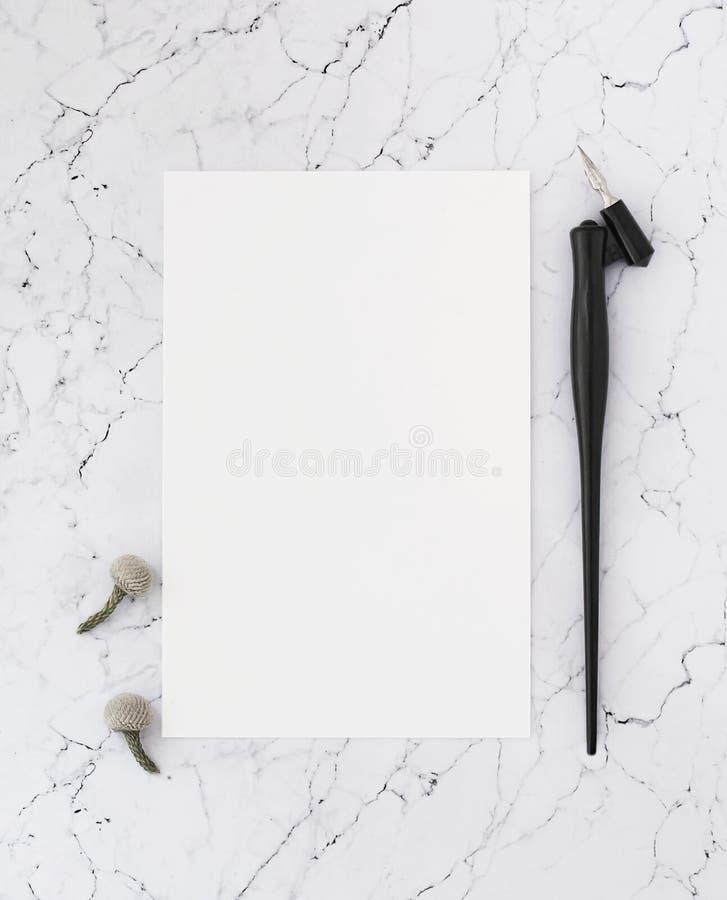 Leeg blad van document op marmer met pen voor kalligrafie stock afbeelding