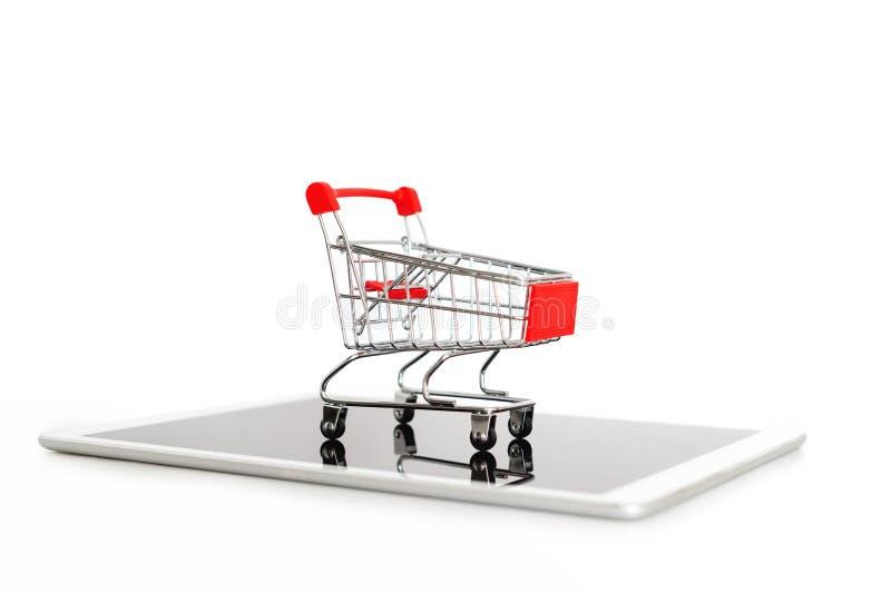 Leeg boodschappenwagentje op digitale die tablet, op witte achtergrond wordt geïsoleerd Online het winkelen en van Internet direc stock foto's