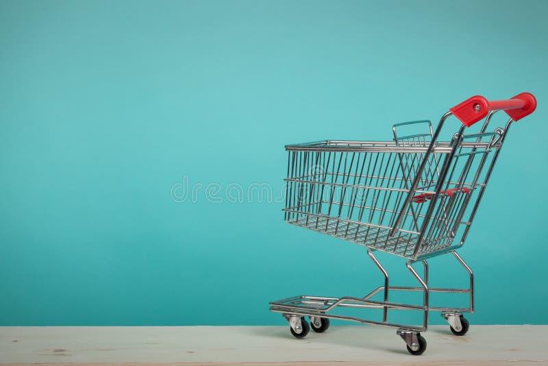 Leeg boodschappenwagentje op houten lijst met groene backround Het concept van het consumentisme Online het winkelen concept royalty-vrije stock afbeeldingen