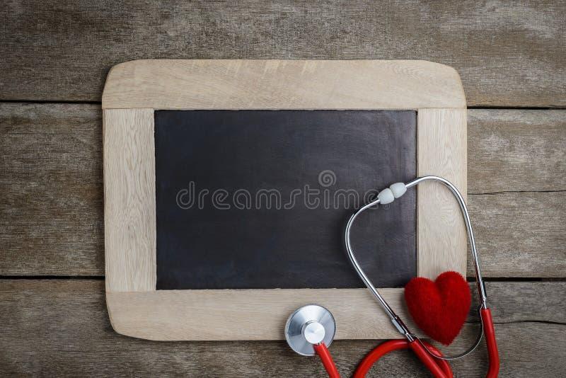 Leeg bord, stethoscoop en rood hart, gezondheidsachtergrond c stock foto