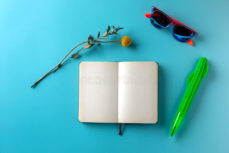 Leeg brochure en potlood en zonnebril op blauwe achtergrond Prototype op zachte lichtblauwe achtergrond royalty-vrije stock afbeeldingen
