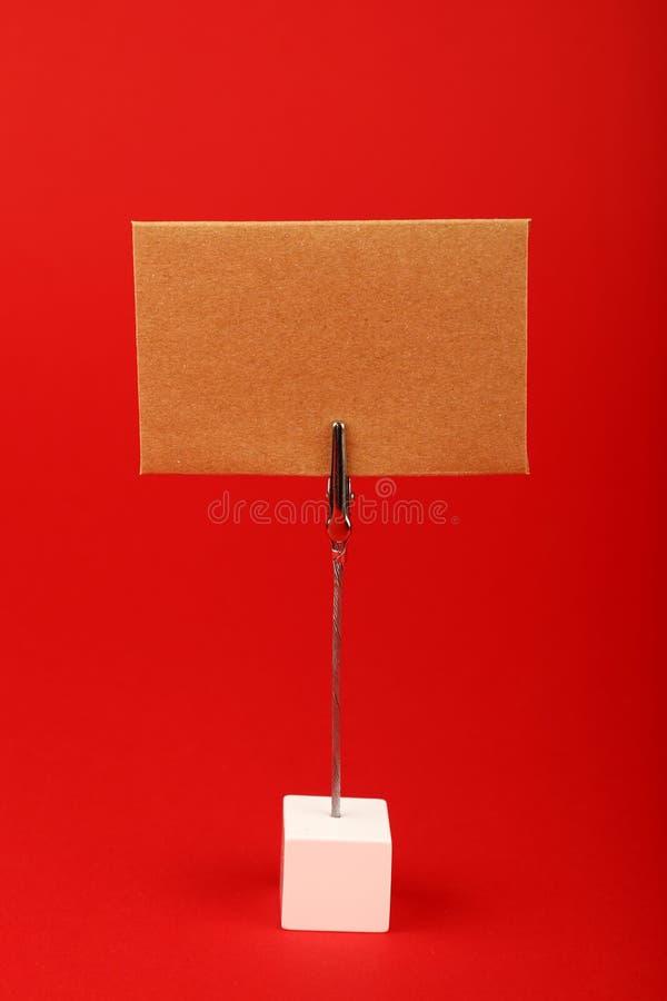 Leeg bruin kraftpapier-document teken over rode achtergrond royalty-vrije stock foto